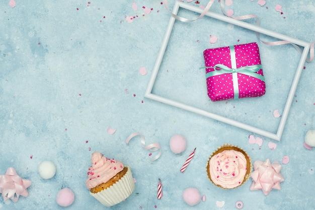 Vista superior do presente de aniversário com cupcakes e espaço de cópia Foto gratuita