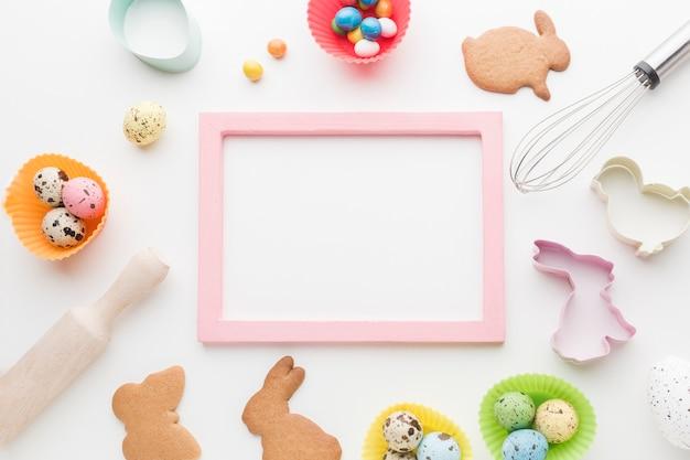 Vista superior do quadro com biscoitos de coelhinho da páscoa e utensílios de cozinha Foto gratuita