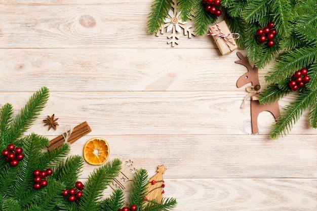Vista superior do quadro feito de galhos de árvore do abeto e decorações de férias em madeira. Foto Premium