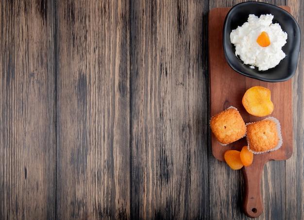 Vista superior do queijo cottage em uma tigela preta com muffins e damascos secos na tábua de madeira rústica com espaço de cópia Foto gratuita