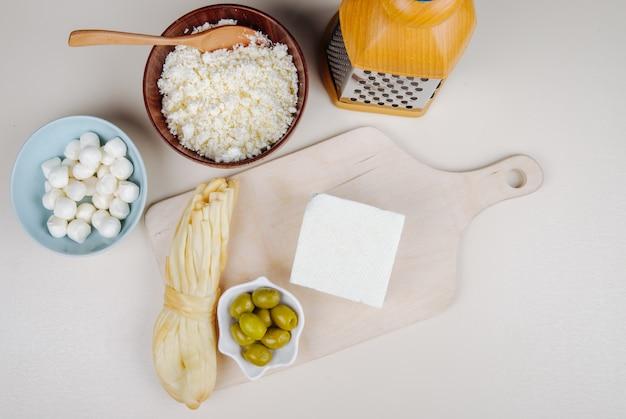 Vista superior do queijo feta com azeitonas em conserva em uma tábua de madeira e queijo de corda, queijo cottage em uma tigela e mussarela com ralador na mesa branca Foto gratuita