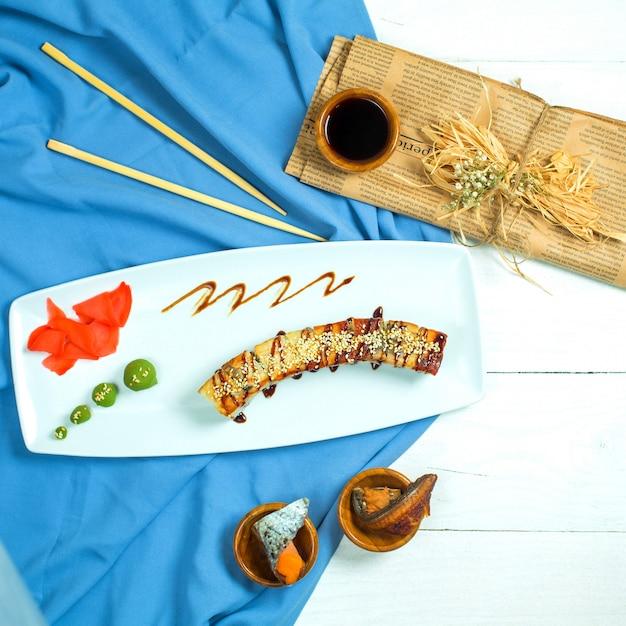 Vista superior do rolo de sushi de cozinha tradicional japonesa com enguia abacate e queijo creme em uma bandeja branca com gengibre e wasabi Foto gratuita