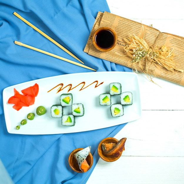 Vista superior do rolo de sushi preto tradicional cozinha japonesa com abacate de arroz e creme de queijo servido com molho de soja, gengibre e wasabi em azul e branco Foto gratuita