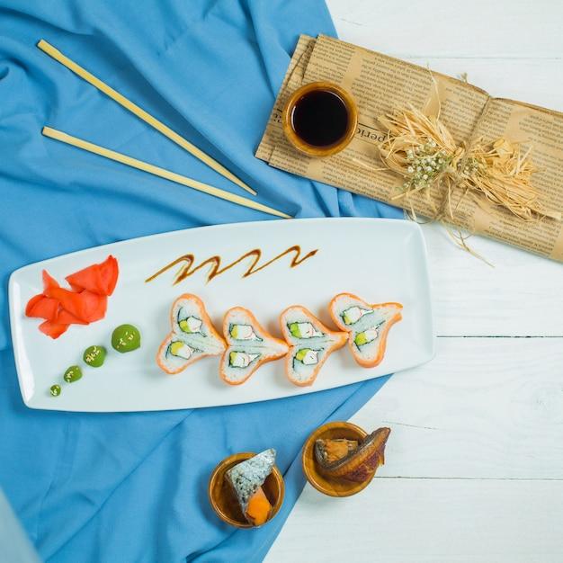 Vista superior do rolo de sushi tradicional da filadélfia de culinária japonesa com salmão abacate de pepino de queijo da filadélfia, disposto em forma de coração no backgrou branco e azul Foto gratuita