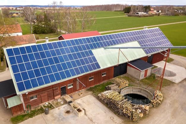 Vista superior do sistema solar azul dos painéis voltaicos da foto no telhado de madeira da construção, do celeiro ou da casa. conceito de produção de energia verde ecológica renovável. Foto Premium