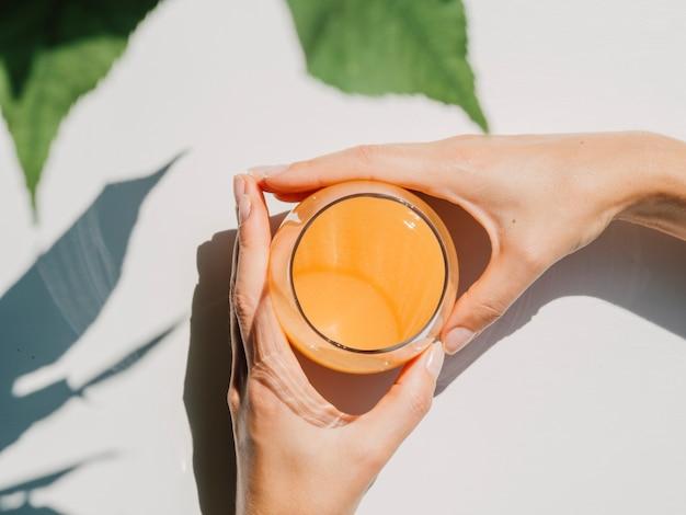 Vista superior do suco de laranja com mãos de mulher Foto gratuita