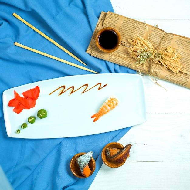 Vista superior do sushi nigiri japonês tradicional com camarão servido com molho de soja e gengibre com wasabi em azul e branco Foto gratuita