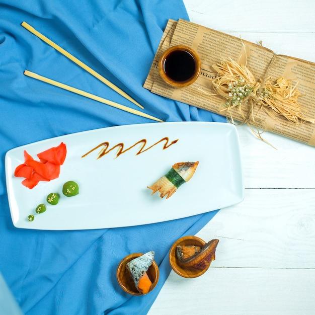 Vista superior do sushi nigiri japonês tradicional com enguia servida com molho de soja e gengibre com wasabi em azul e branco Foto gratuita