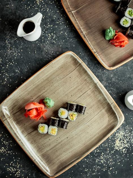 Vista superior do sushi nori com abacate servido com gengibre e wasabi Foto gratuita