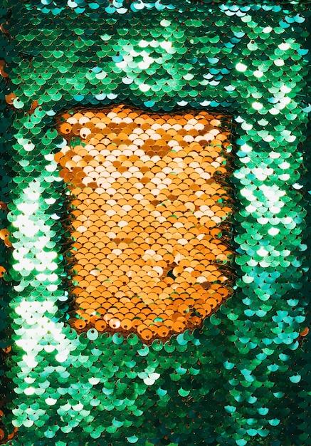 Vista superior do tecido dourado e verde com lantejoulas brilhantes como pano de fundo Foto gratuita