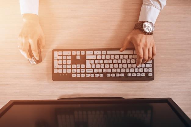 Vista superior do teclado com as mãos dos homens. espaço de cópia de monitor preto grátis para o projeto. brilho quente da luz do sol Foto Premium