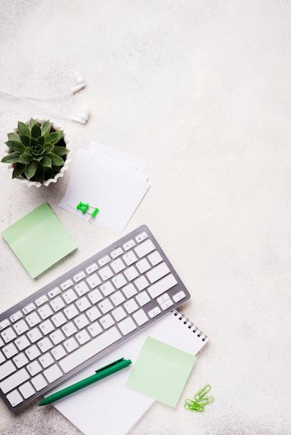 Vista superior do teclado na mesa com planta suculenta e notas autoadesivas Foto gratuita