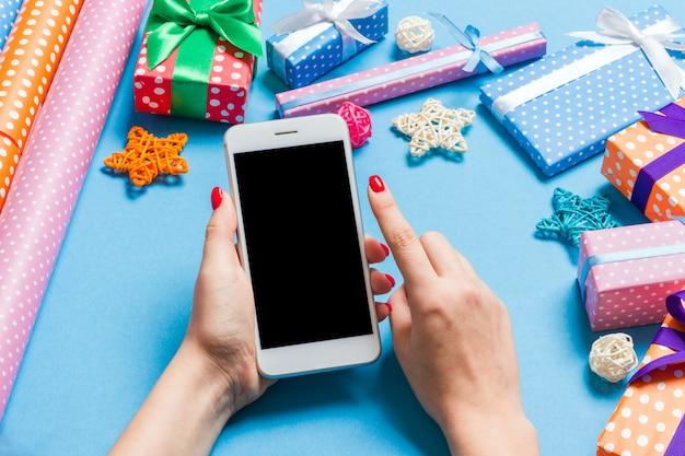 Vista superior do telefone na mão feminina no azul festivo Foto Premium