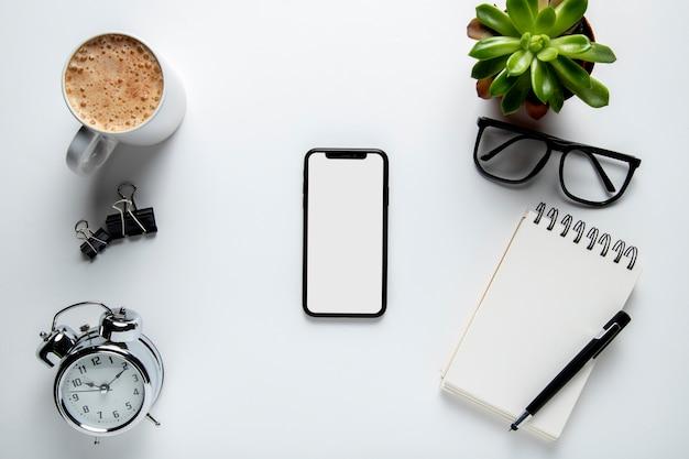 Vista superior do telefone na mesa com o bloco de notas Foto gratuita