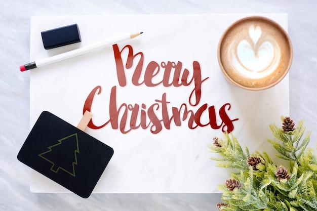 Vista superior do texto feliz natal em mármore com lousa, lápis, folha de pinho borracha ec Foto Premium