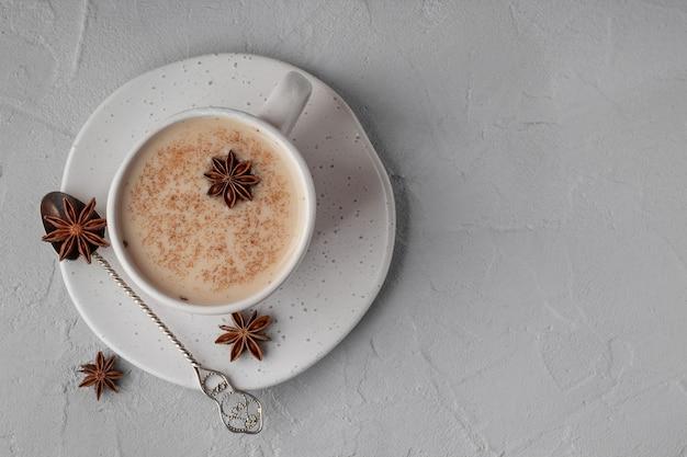 Vista superior do tradicional chá indiano masala com especiarias na taça na mesa cinza, espaço para texto. bebida de reforço de imunidade orgânica Foto Premium
