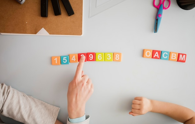 Vista superior do tutor ensinando criança na mesa sobre números e letras Foto gratuita