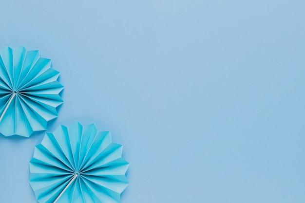 Vista superior do ventilador de papel origami azul no fundo liso Foto gratuita