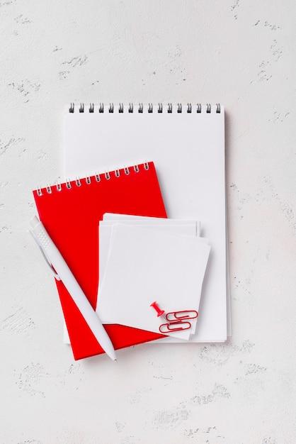 Vista superior dos blocos de notas na mesa com caneta e notas autoadesivas Foto gratuita