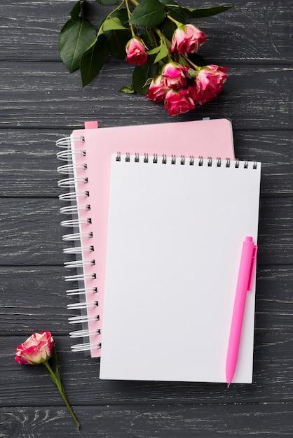 Vista superior dos cadernos na mesa de madeira com buquê de rosas Foto gratuita