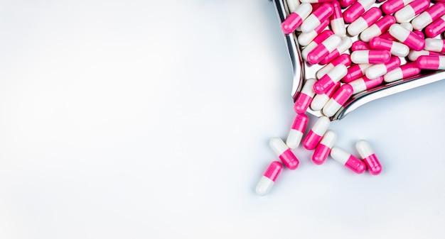 Vista superior dos comprimidos da cápsula rosa-branco na bandeja de drogas. droga antipsicótica. cápsula medicamento para tratamento de depressão. Foto Premium