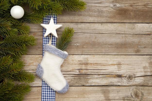 Vista superior dos enfeites de natal e uma meia em uma mesa de madeira com galhos de árvores Foto gratuita