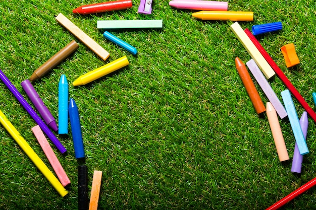 Vista superior dos gizes na grama plástica verde. espaço da cópia Foto Premium