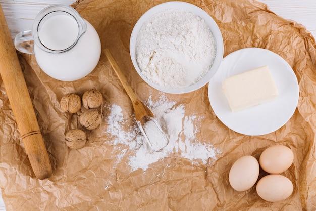 Vista superior dos ovos; queijo; farinha; nozes; rolo de massa no papel amassado marrom Foto gratuita