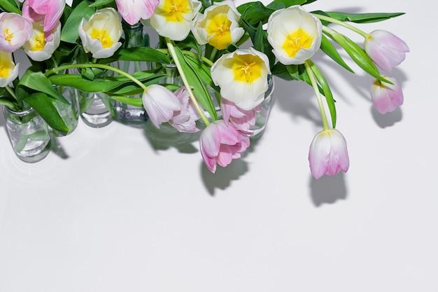 Vista superior dos ramalhetes das tulipas nos frascos de vidro em um fundo branco. Foto Premium
