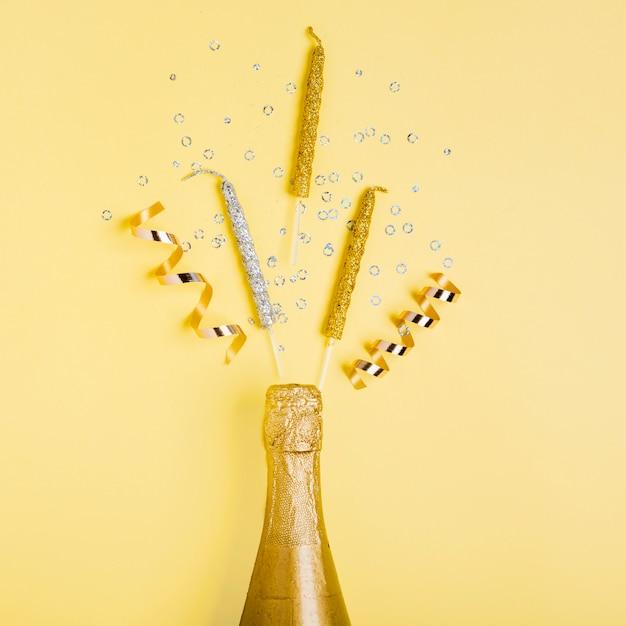 Vista superior dourada garrafa de champanhe e fitas com velas Foto gratuita