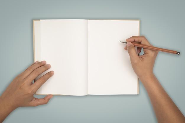 Vista superior - duas mãos segurar um livro vazio espalhar Foto Premium