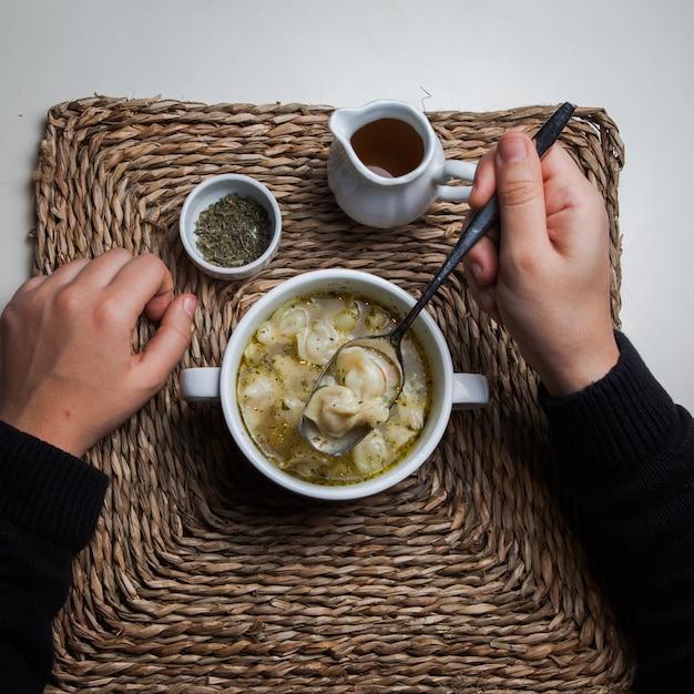 Vista superior dushpara com vinagre e hortelã seca e mão humana em servir guardanapos Foto gratuita