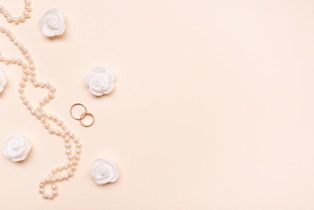 Vista superior elegantes pérolas com anéis de noivado Foto gratuita