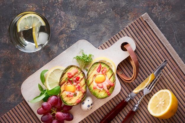 Vista superior em barcos de abacate grelhado com bacon e ovos de codorna Foto Premium