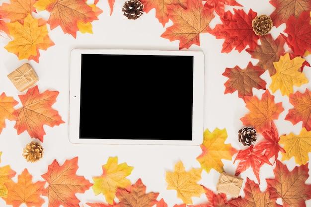 Vista superior em branco tablet decorado com folhas de outono de bordo colorido e caixas de presente Foto Premium