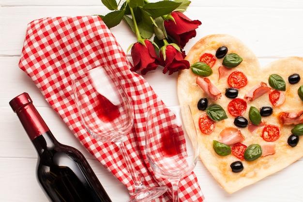 Vista superior em forma de coração pizza jantar arranjo Foto gratuita