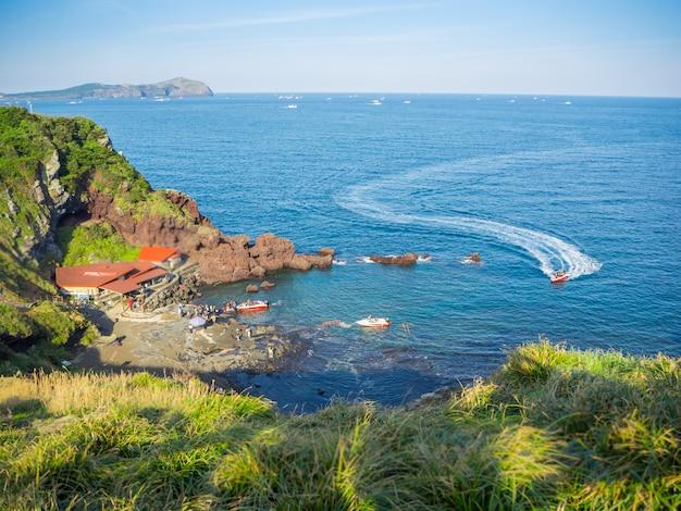 Vista superior em jeju seongsan llchulbong e atividades de turismo para o barco a jato para passear no mar. Foto Premium
