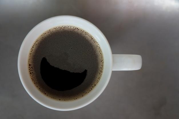 Vista superior engraçado café preto com sorriso símbolo e espuma colocar na mesa de aço inoxidável tempo de relaxamento Foto Premium