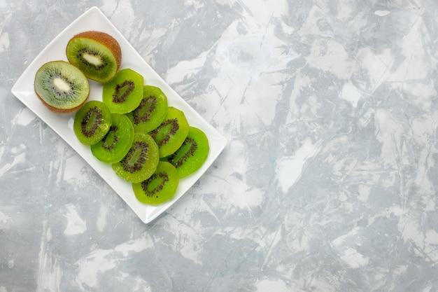 Vista superior fatiada de kiwis frescos dentro do prato no fundo branco claro Foto gratuita