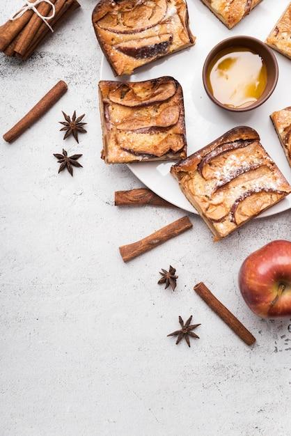 Vista superior fatias de bolo e maçã com paus de canela Foto gratuita