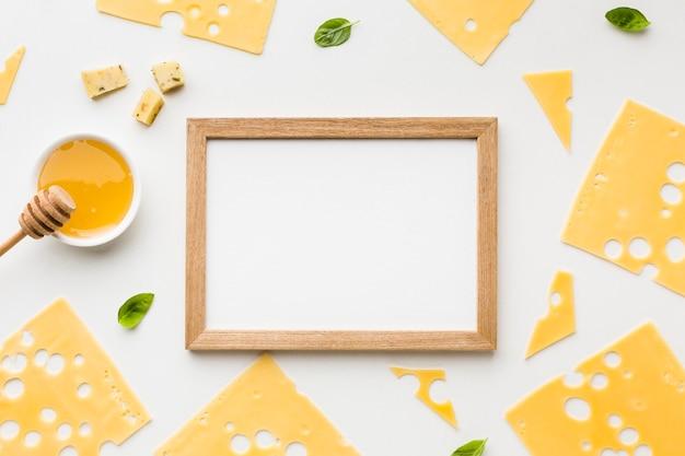Vista superior fatias de queijo emmental com mel e moldura de madeira Foto gratuita