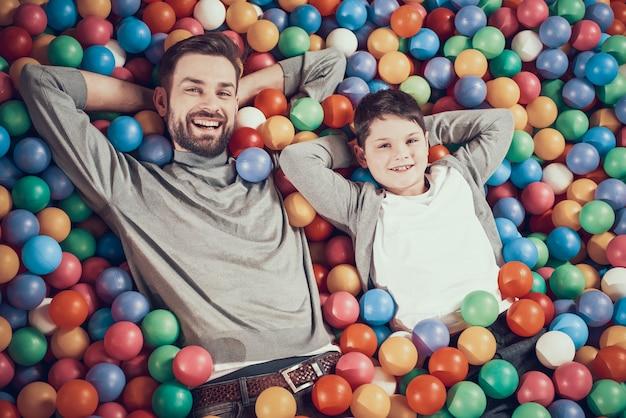 Vista superior, feliz, pai filho, em, piscina, com, bolas Foto Premium