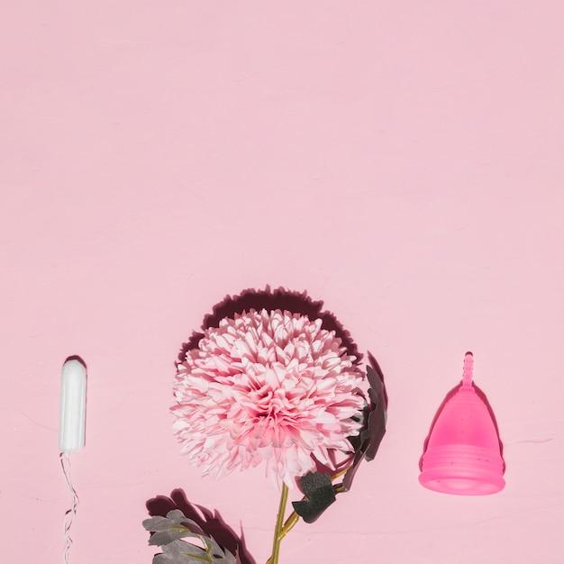 Vista superior flor com tampão e copo menstrual Foto gratuita