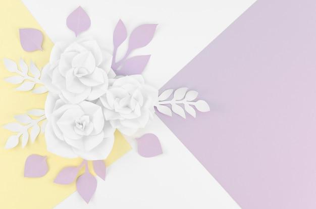 Vista superior flores de papel branco sobre fundo colorido Foto gratuita