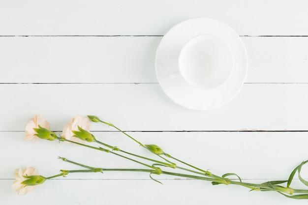 Vista superior flores e copa em fundo de madeira Foto gratuita