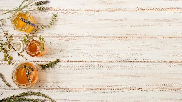 Vista superior, frascos mel, com, folhas Foto gratuita