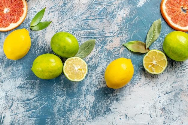 Vista superior frutas cítricas limões toranjas tangerinas na superfície azul e branca Foto gratuita