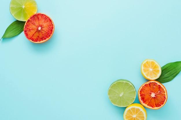 Vista superior frutas cítricas nos cantos Foto gratuita