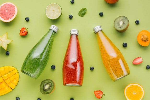 Vista superior frutas e sucos coloridos Foto gratuita