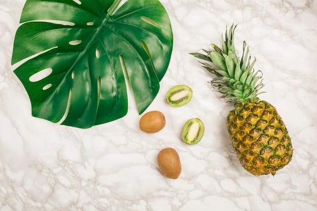 Vista superior frutas tropicais e folhas em mármore Foto gratuita